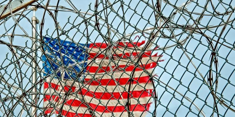 US-flag-behind-fences-800x531